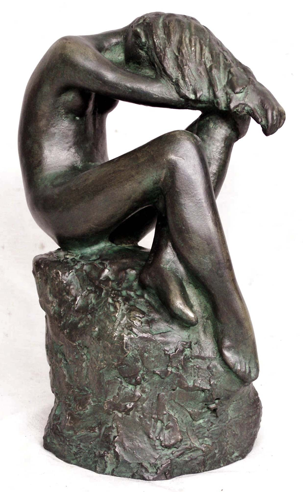 Sculpture of a nude girl seated on a rock