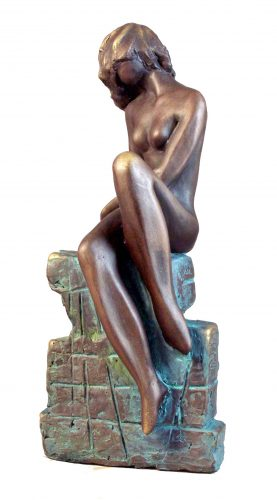 Statuette of a nude girl seated on a wall