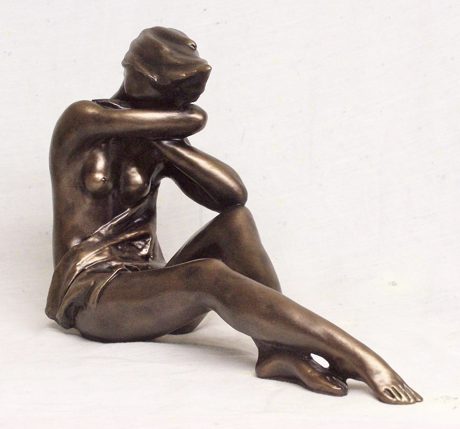 Sculpture featuring a woman seated on floor with hair in the wind