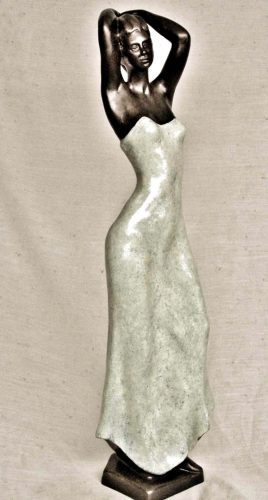 Tall woman with mottled dress and hands on her head