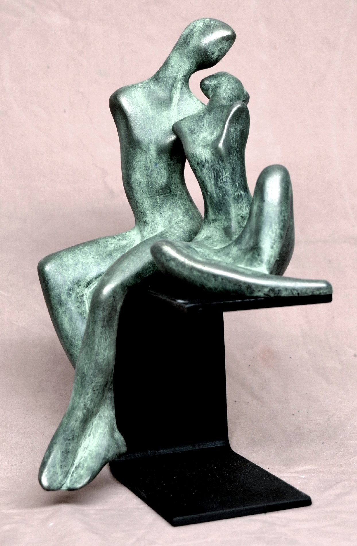 Modern style sculpture of a couple ssitting on an iron base