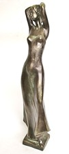 Tall woman sculpture with hands on her head