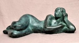 Sculpture of a  nude woman lying on the floor with green patina